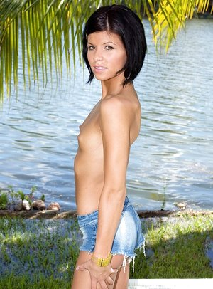 Petite amateur Bella Ryderr undresses on a lounge chair down by the river