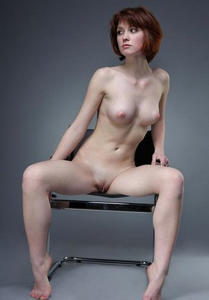 Naked skinny Bretta A poses on a studio chair showing her small perky tits
