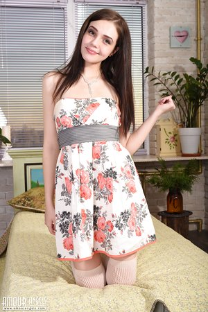 Pretty young Lily doffs her dress to pose nude on her knees in white pantyhose