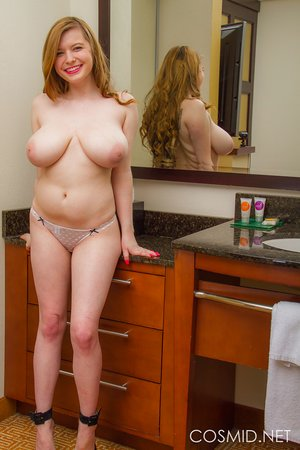 Bug and busty Amanda Love playing with her huge breasts in the bathroom mirror