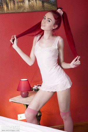 Hot skinny redhead Ariel poses nude on her bed in red fishnet stockings