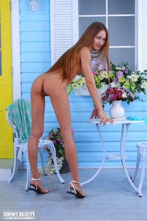 Small titted pretty model Mila on the patio unwrapping to squat & opened up naked