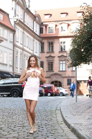 Harmless looking teen strips off her dress and walks nude down a street