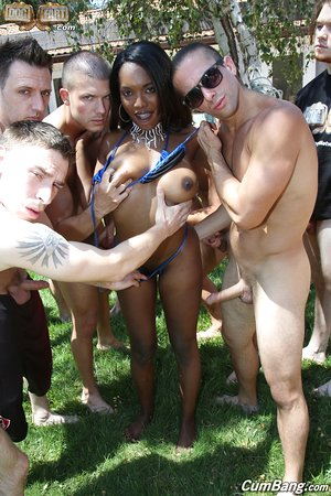 Busty black girl Daya Knight gets on her knees in the backyard for a blowbang