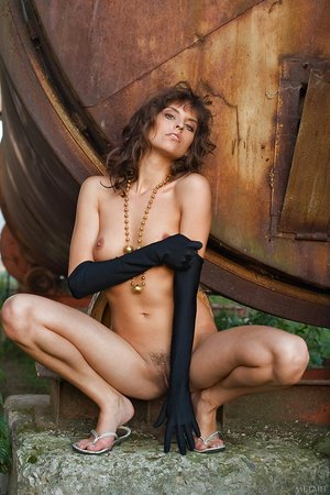 Classy Caucasian chick Kati B poses among rusty machinery in long velvet gloves