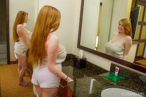 Busty redhead Amanda Love lets her massive big tits hang out in the bathroom