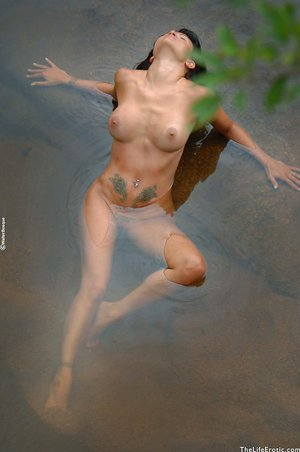 Arousing Laura shows off her incredible bare assets while bathing in a lake