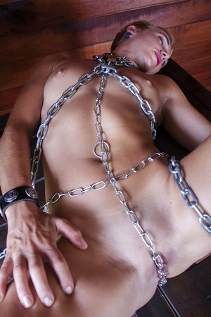 White chick with short hair and natural breasts models nude in chains