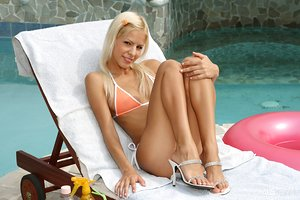 Lean blonde girl Boroka rams a huge sex toy up her tight vulva by the pool