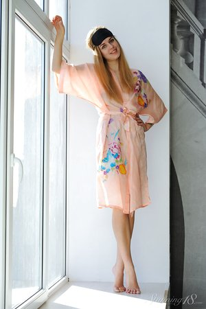 18 year old teen with long hair shows her naked body on a window sill