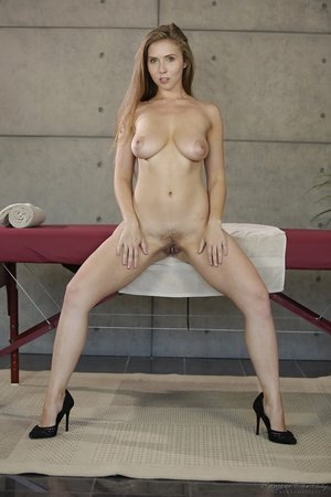 Elegant Lena Paul peels off down by massage table to display tits and bald pussy