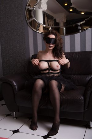 Busty brunette Judith Able takes off her blindfold and stockings on loveseat