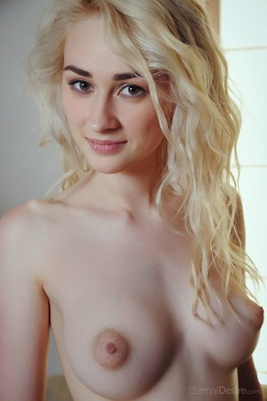 Topless blonde girl Innes A slides her pantyhose over her thick ass