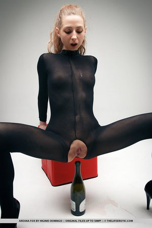 Fetish girl Areana Fox in crotchless catsuit stuffs a wine bottle in her twat