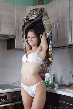 Thin amateur Shivali displays furry underarms and beaver in her kitchen