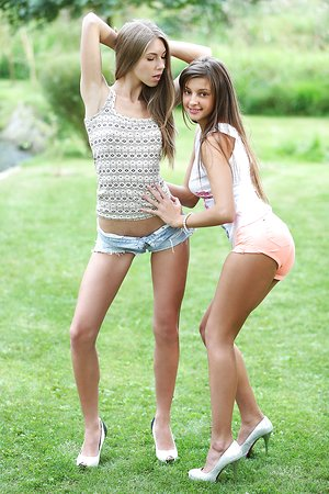 Teen girls share a smooch as they help each other unwrap on the lawn