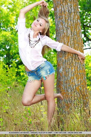 Handsome teen girl Alessandra A heads to the woods to pose nude against a tree