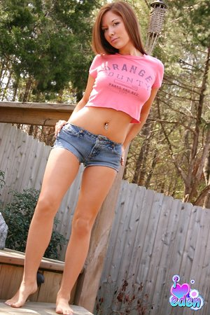 Beautiful teenage brunette posing outside in lil' booty cut-offs flaunting her torrid ass