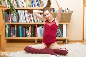 Young solo girl shows her thin body in the nude after bookcase