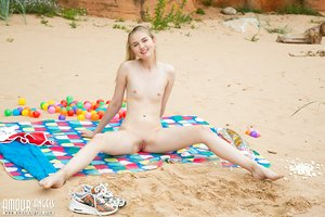 Barely legal teen reveals her flat chest and bald honeypot on a beach blanket