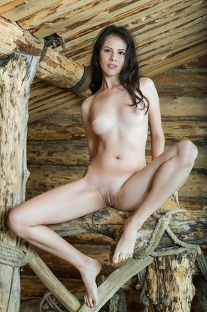 Solo woman with luxurious brown eyes poses naked in a cabin loft