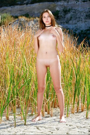 White girl with beautiful eyes poses naked at the beach in a choker