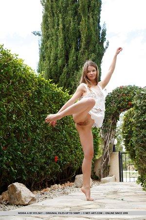 Adorable teen Nedda A grabs her tight ass while posing nude in courtyard