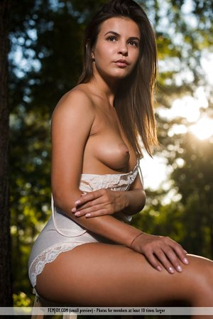 Young looking brunette Arina B doffs underwear for nude poses beside woods