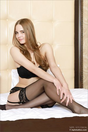 Luxurious young brunette in black stockings & garter posing on her knees naked