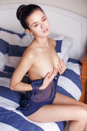 Dark haired beauty Carmen Summer holds a breast while modeling in the nude