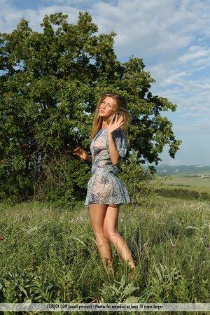 Cute teen girl April E blows a smooch while posing nude in farmer's field