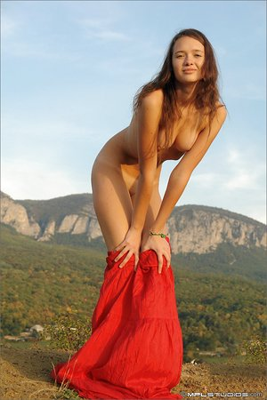 Teen beauty glides off her red skirt to model bare in the foothills